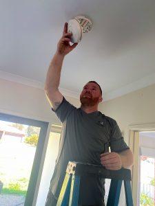 electrician installing smoke alarm